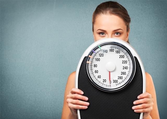 体重計を手に持っている女性