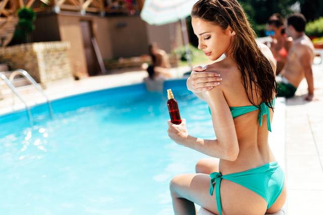 水着姿の女性が日焼け止めを塗っている