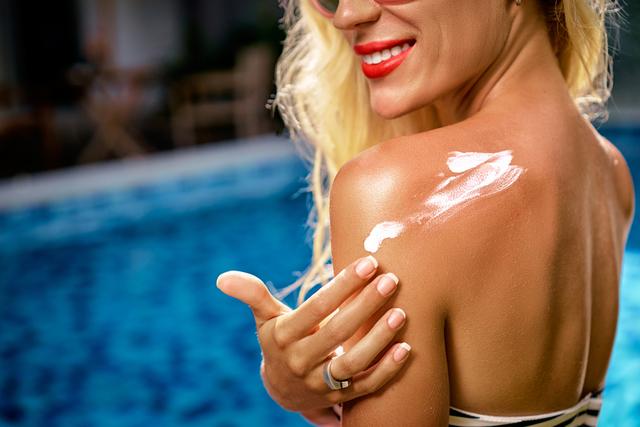 プールサイドで水着姿の女性が日焼け止めを塗っている