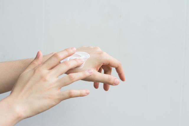 クリームを塗っている女性の手
